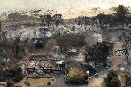 A house damaged by a bushfire is seen from a helicopter in Boomer Bay, near Dunally in Tasmania