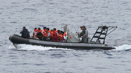 Asylum-seekers who were saved from a capsized boat are brought ashore on Christmas Island yesterday