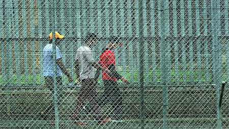 People walk behind the barbed wire fences at the Villawood Immigration Detention Centre in Sydney