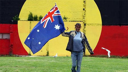 A woman carries the national flag in front of an Aboriginal flag